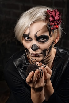 Soft focus portrait of female face with sugar skull makeup holding spider in hands. face painting art.