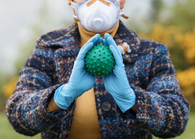 Soft focus of portrait of a woman wearing a white and red face mask, blue gloves,  holding coronavirus in her hands