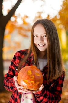 Soft focus portrait of a young girl with a pumpkin