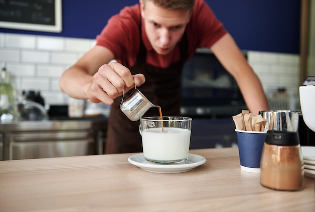 Soft focus on pouring hot coffee into whipped milk against blurred background of handsome young barista behind bar counter