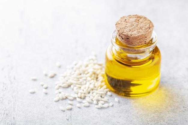작은 병에 든 소프트 포커스 참기름과 건강한 식생활을 위한 씨앗