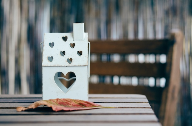 Soft focus shot of a house shaped lantern with heart holes on a wooden table