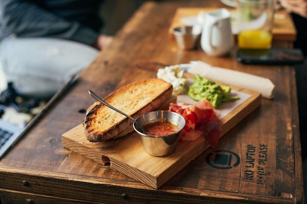 Soft focus shot dell'uomo che mangia una deliziosa colazione enorme al fresco ristorante o bar, mette guacamole o avocado sparsi in cima al pane tostato di segale