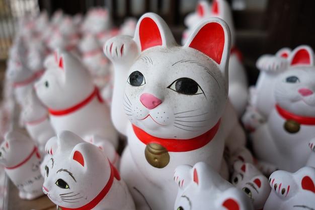 Снимок пыльной японской кошки-счастливчика (манэки-нэко) в мягком фокусе.
