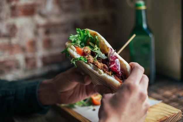 クールなレストランやカフェでおいしい朝食を食べている男性のソフトフォーカスショット、ライ麦パンのトーストの上にワカモレやアボカドを塗る