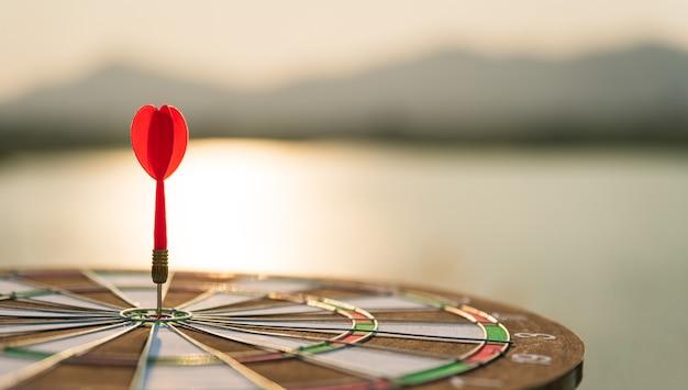 Soft focus shot red darts arrows in the target center on dark sky background