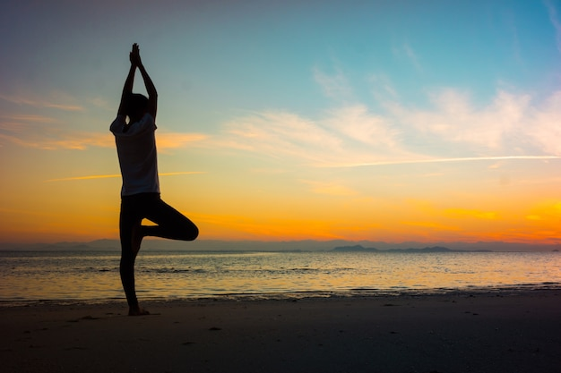 Soft focus silhouette young woman practicing yoga on the beach at sunset