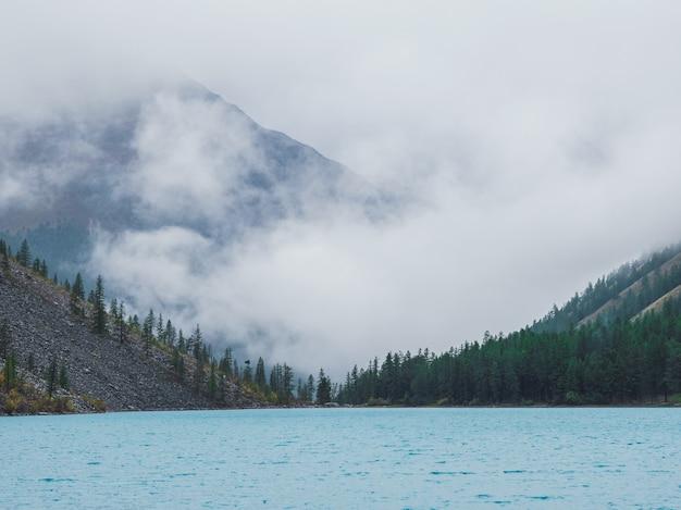 ソフトフォーカス。濃霧の中の山の湖に沿ったモミの丘の中腹のシルエット。青い水の中の針葉樹の反射。涼しい早朝の高山の静かな風景。幽霊のような雰囲気の風景。