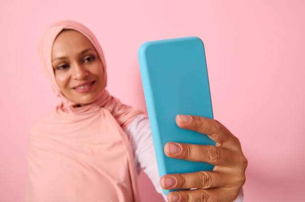Soft focus on the smartphone in blue cover in outstretched arms of arab muslim woman wearing traditional religious islamic outfit, pink hijab,and smiles with toothy smile making self-portrait, selfie