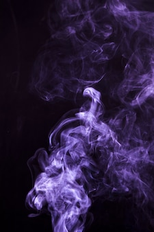 Soft focus of smoke swirling on black background
