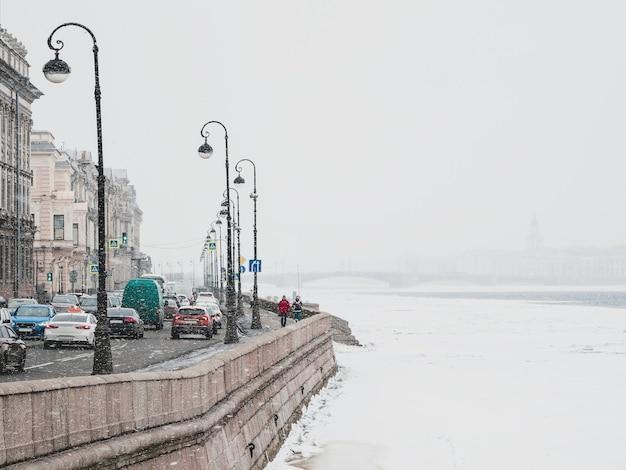 ソフトフォーカス降雪。サンクトペテルブルクの春の降雪。ネヴァ川の堤防での交通渋滞。ロシア。
