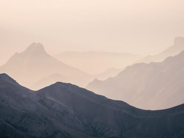 ソフトフォーカス。山の風景の柔らかなピンクの夕日。山のシルエットと素晴らしいピンクの夕日。