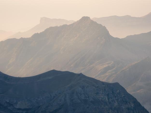 ソフトフォーカス。山の風景の柔らかなピンクの夕日。日没時の夕方の山のシルエット。
