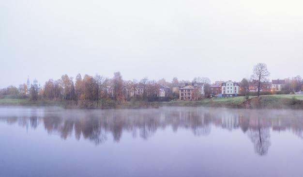 ソフトフォーカス。村は霧の中にあります。ロシア、ガッチナ市近くの湖の表面の朝もや。全景。