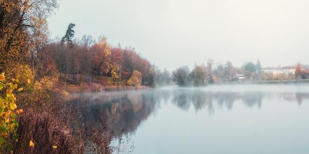 Мягкий фокус. деревня в тумане. панорамный вид утренней дымки над поверхностью озера недалеко от города гатчина, россия.