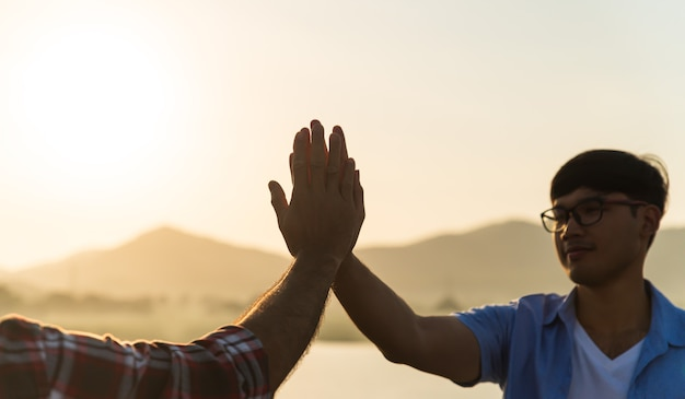 Soft focus of two man hand giving fist bump in front of mountain during sunset Premium Photo