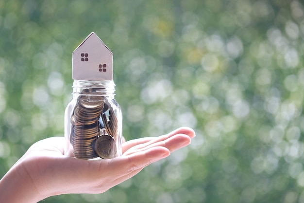 Soft focus of woman hand holding model house on coins money in glass bottle on natural green background, business investment and real estate concept