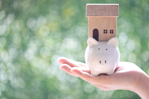 Soft focus of woman hand holding piggy bank wth model house on natural green background, business investment and real estate concept