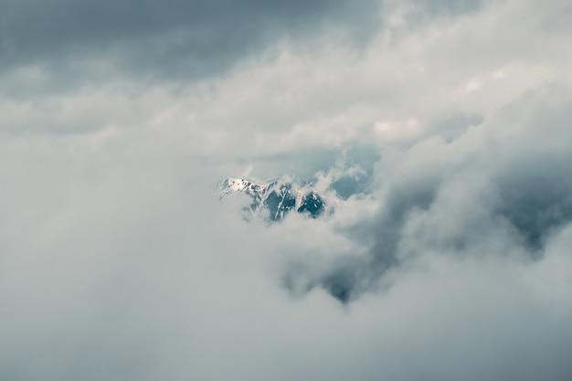 ソフトフォーカス。低い雲の上に大きな雪山の頂上がある素晴らしいミニマリストの風景。曇り空に大きな雪の山頂がある大気のミニマリズム。
