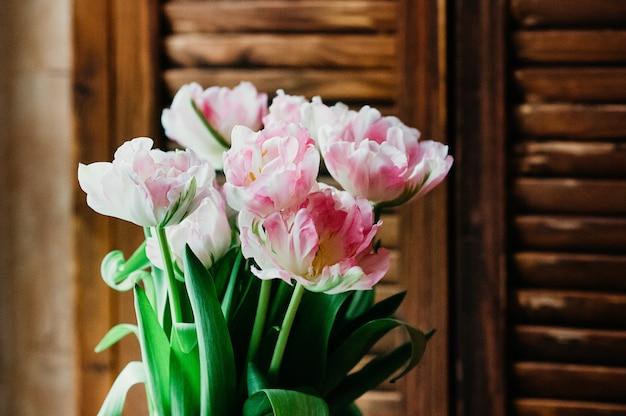 ピンクの花のソフトフォーカスの花束木製ジャロジー素朴なスタイルのクローズアップビュー屋内