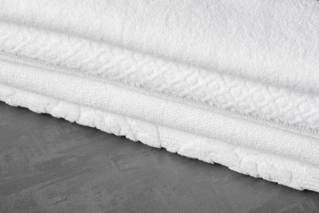 A soft folded bath towel on the gray surface, close-up