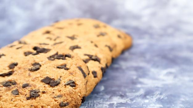 Мягкое свежеиспеченное шоколадное печенье на серой мраморной кухонной столешнице. американская традиционная сладкая выпечка, вкусный домашний десерт. кулинарный фон. копировать пространство