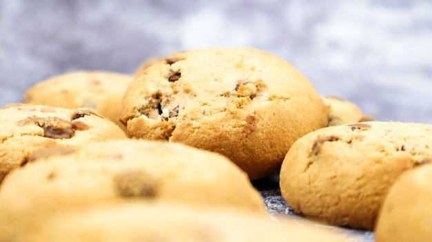 Мягкое свежеиспеченное шоколадное печенье на серой мраморной кухонной столешнице. американская традиционная сладкая выпечка, вкусный домашний десерт. кулинарный фон. выборочный фокус