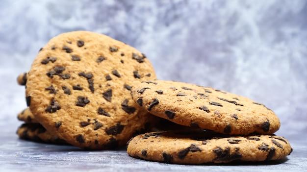 회색 대리석 주방 조리대에 갓 구운 부드러운 초콜릿 칩 쿠키. 미국 전통 달콤한 패스트리, 맛있는 수제 디저트. 요리 배경입니다. 프리미엄 사진