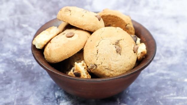 회색 대리석에 갈색 토기 접시에 초콜릿 칩을 넣은 갓 구운 부드러운 쿠키. 미국 전통 달콤한 패스트리, 맛있는 수제 디저트. 요리 배경입니다.