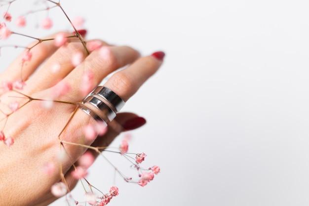 Мягкие нежные фото руки женщины с большим кольцом красного маникюра держать милые маленькие розовые сушеные цветы на белом.