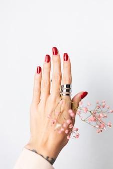Morbida foto delicata della mano della donna con il grande anello rosso manicure tenere graziosi piccoli fiori secchi rosa su bianco.