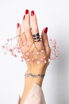 Soft gentle photo of woman hand with big ring red manicure hold cute little pink dried flowers on white.
