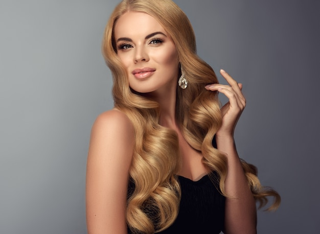 Soft gesture of slender fingers is opening excellent curls of blonde hair and shows earring made from glittering stones.tender smile on the blonde haired woman.wavy hair.beauty and elegance.