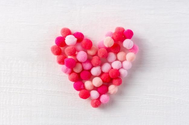 Мягкое сердечко из маленьких шерстяных помпонов в знак нежной любви на белом деревянном столе