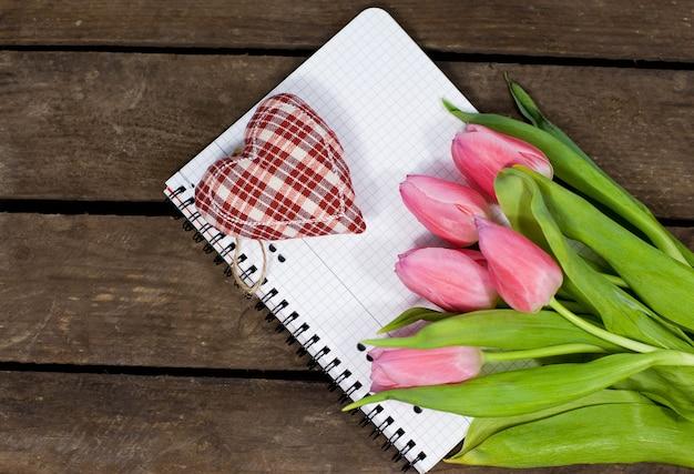 부드러운 마음, 노트북 및 나무 배경에 튤립 꽃다발