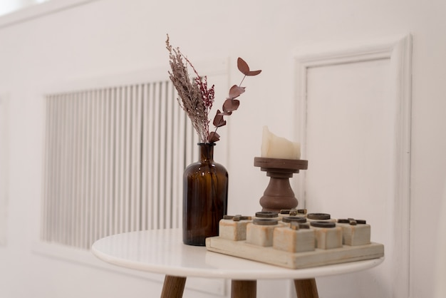 Soft home decor made of glass vase with spikelets and wood play on white table. interior.