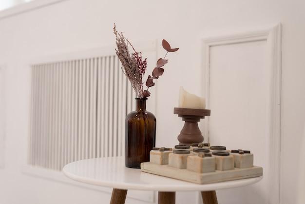 흰색 테이블에 작은 이삭과 나무가있는 유리 꽃병으로 만든 부드러운 가정 장식. 내부.