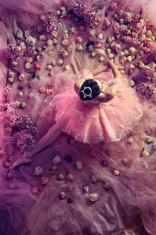Soft at home. top view of beautiful young woman in pink ballet tutu surrounded by flowers. spring mood and tenderness in coral light.  concept of spring, blossom and nature's awakening.