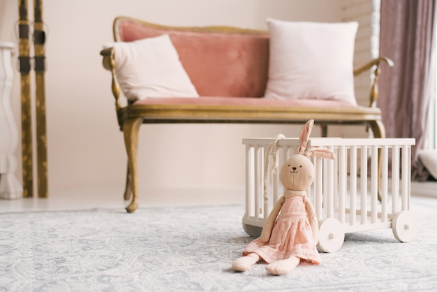 Soft homemade toy bunny in a pink dress in the children's room