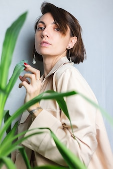 Morbido ritratto al coperto della donna caucasica gentile che indossa un abito beige senza reggiseno, in posa dietro la pianta tropicale della palma, grigio.