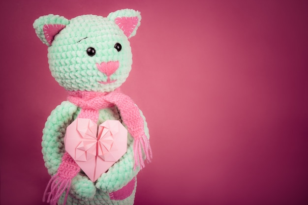 Soft knitted cat and valentine card on pink background.