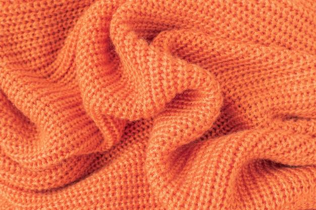 Soft knitted fabric from orange fluffy yarn.