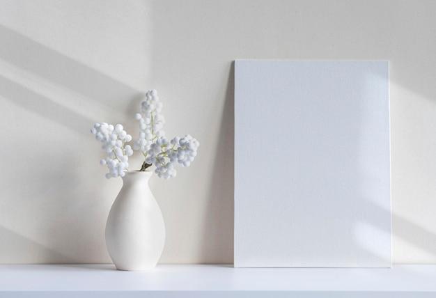Мягкая светлая композиция с чистым холстом или листом, вазой, декоративным комнатным растением на столе. интерьер белой комнаты, минимальный макет с пространством для текста
