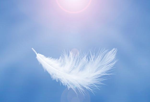Мягкое легкое белое перо, парящее в голубом небе абстрактное перо, летящее в небесах