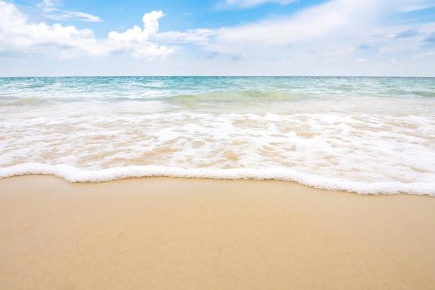 푸른 하늘과 모래 해변에 부드러운 바다 파도.