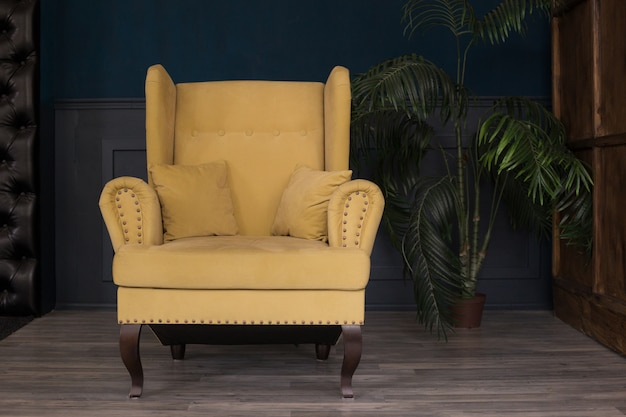 Soft ocher armchair in cabinet with navy blue walls next to flower