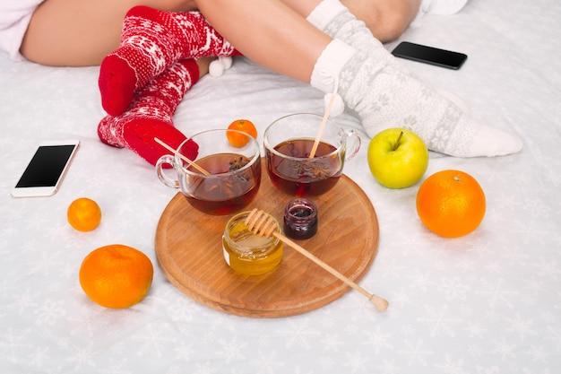 女と男の携帯電話と果物が付いているベッドの上の柔らかい写真。暖かいウールの靴下のカップルの女性と男性の足。クリスマス、愛、ライフスタイルのコンセプト