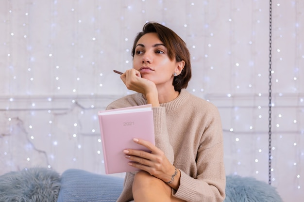 Soft photo of woman in comfy sweater and wool socks at home sit on bed at winter time holding notebook sign 2021