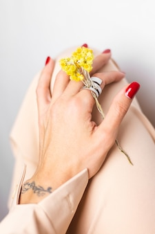 Foto morbida di manicure rossa mano donna, anello al dito, tenere grazioso fiorellino giallo secco, bianco.
