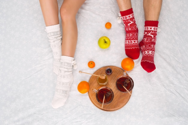 Soft photo of woman and man on the bed with cup of tea and fruits, top view point. female and male legs of couple in warm woolen socks.